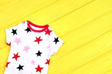 Baby stars print soft t-shirt. Baby boy or girl short sleeve bodysuit on yellow wooden background.