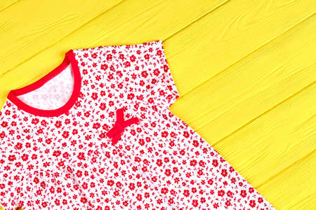 Toddler girl beautiful organic sundress. Little girl adorable patterned dress on yellow wooden background, top view.