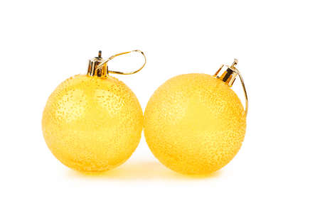 Two textured yellow Christmas balls. Couple of beautiful round Christmas toys isolated on white background. Traditional Christmas ornaments. Stock Photo