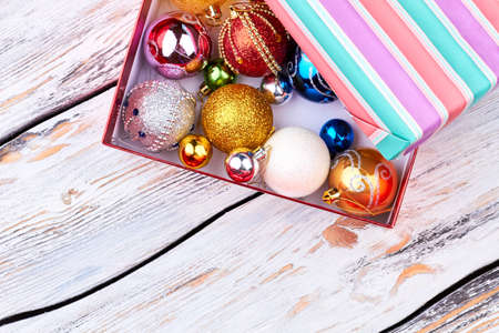 Different shiny Christmas balls in gift box. Christmas decoration toys in open striped gift box on vintage wooden background, top view.