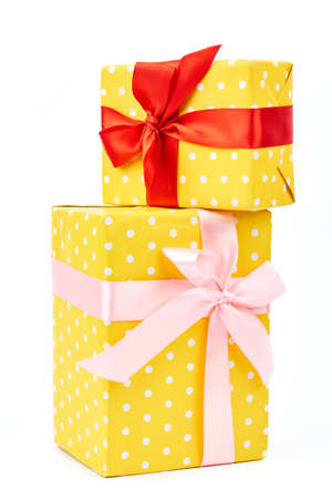 Two yellow dotted gift boxes. Presents are packed in colored paper. Polka-dot pattern tied with a beautiful pink and red ribbons over white background. Stock Photo