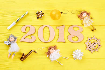 Wooden number 2018 and Christmas ornaments. Wooden numbers forming the number 2018 for the new year 2018 with angels, bows on a yellow wooden background. Christmas 2018 background.