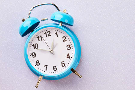 Blue retro alarm clock on winter background. Classic mechanical bell clock on blue dotted background and copy space. Vintage alarm clock.