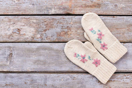 Pair of female hand mittens on wooden background. Woman white woolen knitted gloves on old wooden background, copy space.