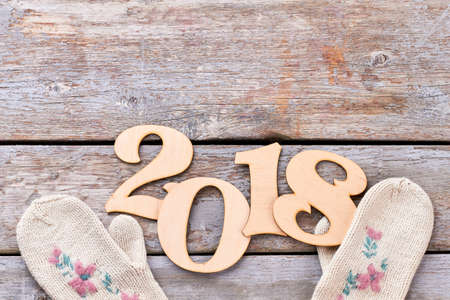 Cut out wooden number 2018 and gloves. Handmade wooden digit 2018 and white knitted mittens on old wooden background, copy space. New Year 2018 concept.
