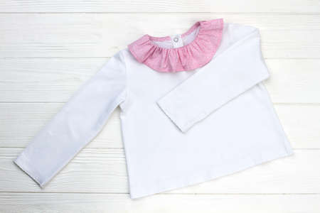 Pajama jacket on wooden shelf. Lightweight garment with beautiful collar. Girls style, white and pink. Stock fotó