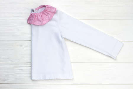 Girls pajama folded in half. White cotton jacket with pink ruffle collar. Cute and cozy sleepwear for children.