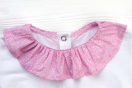 Ruffle collar of sleepwear jacket. Pink and white cotton textile. Cute pajama top for girls. Stock fotó