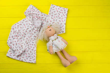 Girls clothes and stuffed doll on yellow wooden background. Top with floral print and ruffles, loose pants. Gift for little princess.