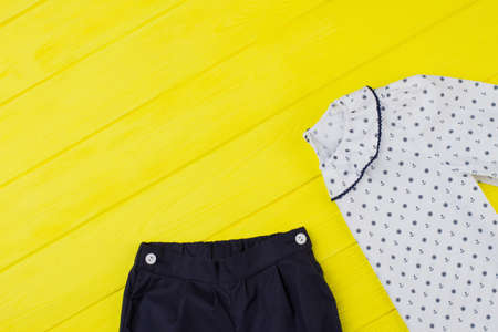 Girls pants and blouse. Good combination of navy and white, completed with sailor pattern. Sleeping garments on yellow table.