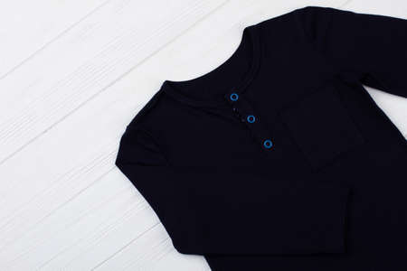 Plain long sleeve t-shirt with button-up crew neck. Black cotton and blue fasteners. Casual garment on white wooden background.