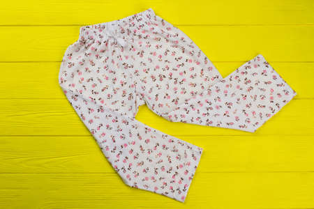 Roomy pants with floral print. Bottom sleeping garment on yellow wooden background. Nightwear for girls.