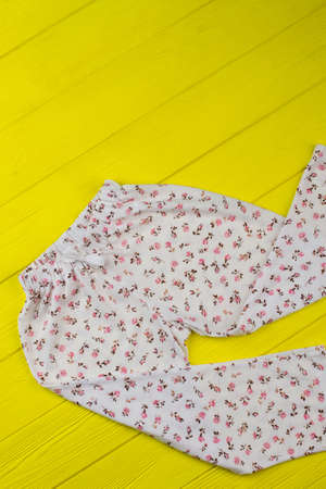 Crumpled pants on yellow background. Loose-fitting garment with floral pattern. Girls clothes for sleeping.