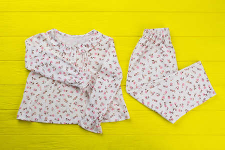 Floral top and pants on yellow table. Soft lightweight cotton for summer nights. Comfy and roomy pajama set for girls. Stock Photo