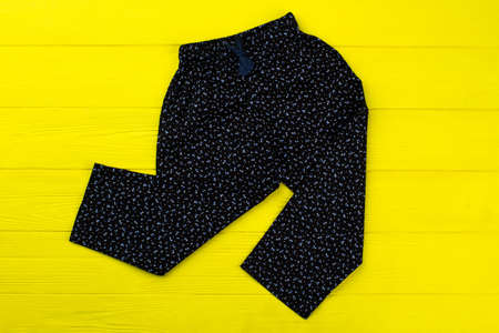 Floral pants on yellow rack, top view. Stylish loose-fitting garment for comfortable lounging. Girls clothing line.