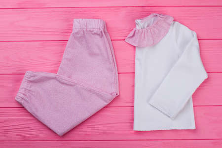 Pink and white pajama set on wooden background. T-shirt with ruffle collar and pants. Snug and soft sleepwear for toddler girls. Stock fotó