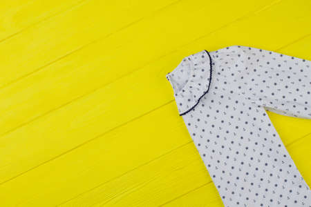 White nightie with collar decorated with edging and sailor pattern. Colorful yellow background. Discount on girls collection.