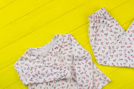 Girlish pajama set on yellow. Cute floral print over white fabric. Top and pants on wooden display at the shop.