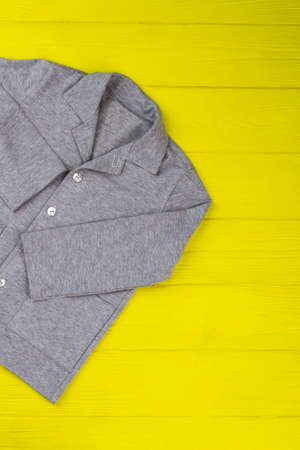 Gray melange shirt on yellow wooden rack at the store. Simple and elegant design. Boys clothing item. Stock Photo