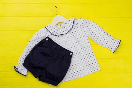 Blouse and shirt on yellow background. Anchors and handwheels pattern. Sailor pajama set for little girls. 스톡 콘텐츠