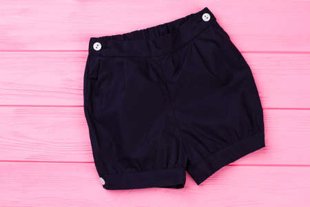 Navy shorts on pink wooden background. Bottom garment with white buttons. Toddler kids clothes.