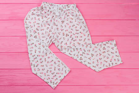 Loose pants on pink background. Garment decorated with floral pattern print. Pajamas bottom for young girls.