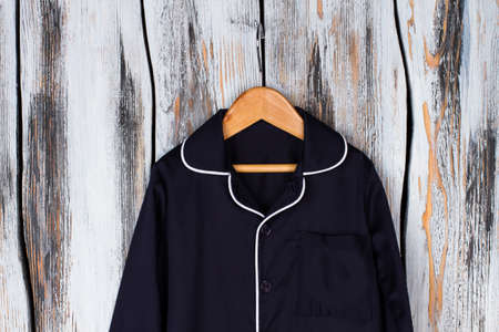 Navy shirt with white edging. Rounded collar and breast pocket. Classic style and simple design of pajama. Stock Photo