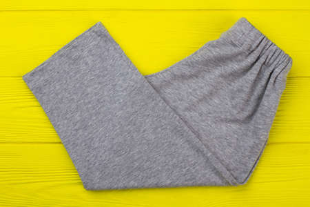Gray melange pants on yellow. Loose-fitting garment made of cotton. Perfect for lounging and sleeping.