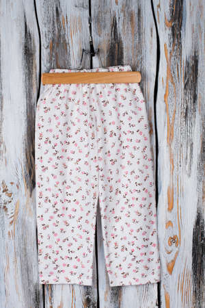 Floral pants on wooden hanger. Lovely roomy garment for comfortable sleeping in summer nights.