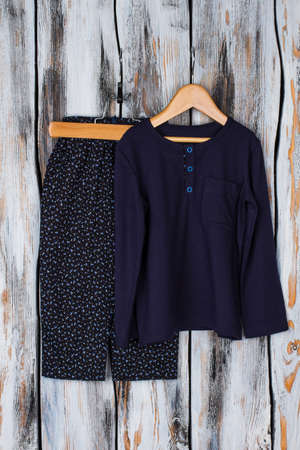 Pajama set on rustic background. Floral pants and navy top on wooden hangers. Best nightwear for children. Stock Photo