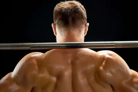 Professional athlete lifting a barbell. Sweat over relief muscular body. Squats and weightlifting.