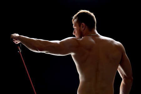 Handsome man working out with resistance band over black background. Perfectly shaped arm and back muscles.