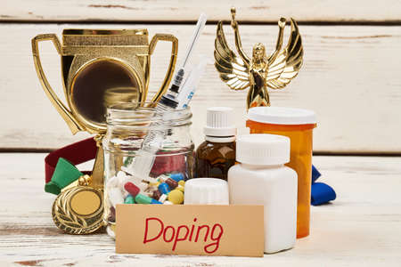 Doping medications and trophy. Drugs to enhance athletic performance. Unfair victory and crime in sports. Stock Photo