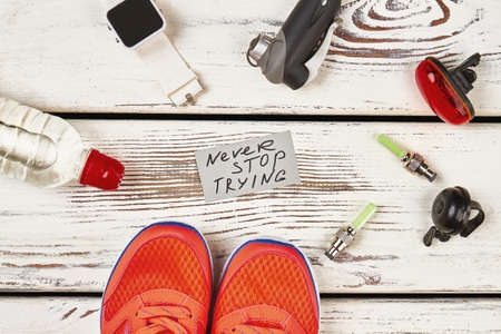 Bicycle equipment, water and sneakers. Note with Never stop trying lettering. Encouragement for tired sportsman. Stockfoto