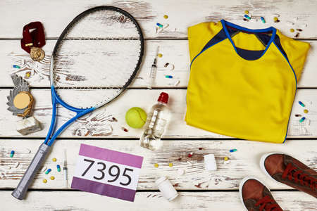 Tennis players uniform and racquet on wooden table. Using banned drugs to win competition. Unfairly earned trophy and medals.