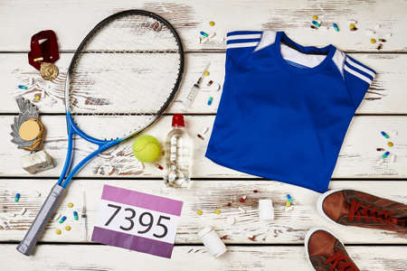 Racquet, shirt, sneakers and number on wooden table. Tennis equipment, awards and spilled drugs. Usage of doping, cheating in sports. Banco de Imagens