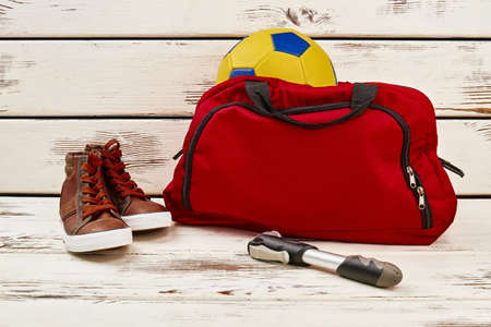 Gym bag with soccer ball, sneakers and pump on wooden table. Sportswear and equipment for physical activity. Archivio Fotografico