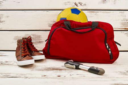 Sac de sport avec ballon de foot, espadrilles et pompe sur la table en bois. Vêtements de sport et équipement pour l'activité physique.