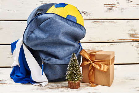 Backpack, soccer ball and uniform on wooden background. Christmas gift for son that loves football game. Stock fotó