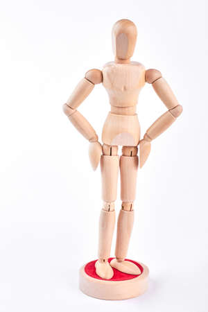 Wooden mannequin with hands on hips. Yellow wooden figure standing on white background. Wooden human dummy.