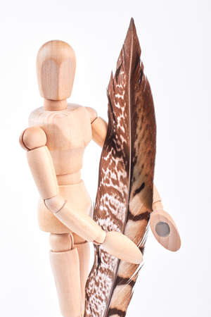 Birds feather in wooden dummy hands. Image of human wooden mannequin with bown feather, isolated on white background.