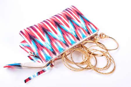 Cosmetics bag and bracelets. Patterned bag for make up and golden bracelets on white background.