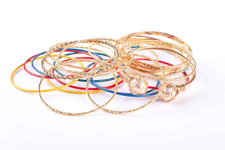 Golden bracelets on white background. Collection of female fashion wrist bands. Women hand accessories.
