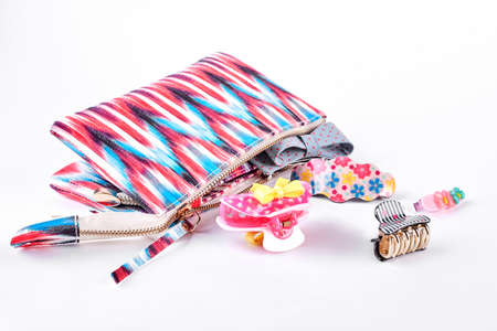 Cosmetics bag with hair clips. Patterned pouch and hair clips on white background.