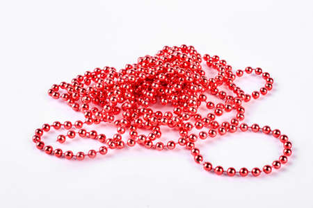 Red beads garland on white background. Beautiful red beaded necklace. Red decoration beads on white background.