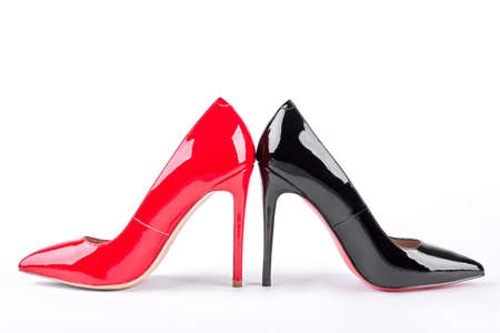 Red and black lacquered high heels. Female elegant leather high heels over white background. Woman trendy shoes.
