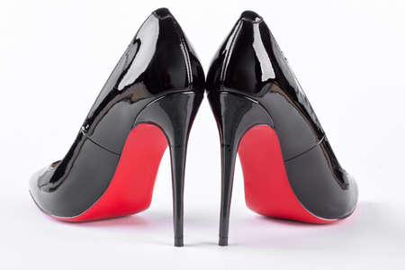 Para nowych czarnych szpilek na białym. Kobiece nowe buty louboutin, widok z tyłu. Christian Louboutin z czerwonymi podeszwami. Stylowe obcasy kobiety. Zdjęcie Seryjne