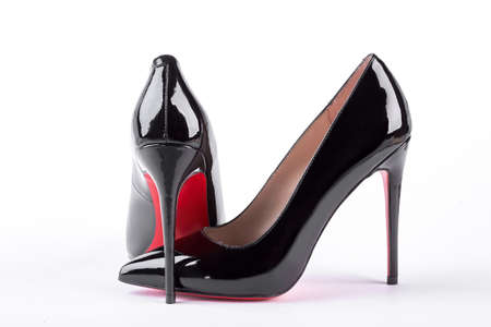 Woman black louboutin on white background. Classic woman high heels on white background. Female stylish outfit.