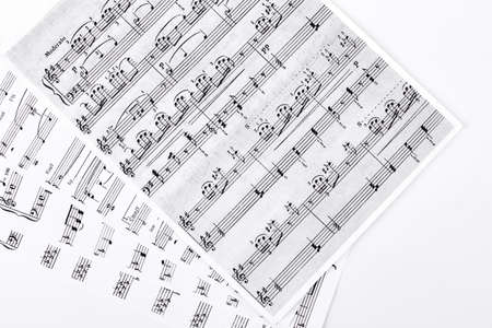 Musical notes on white background. Sheets with musical notes on white background. Music and composition concept. Archivio Fotografico