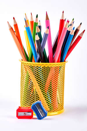 Pencils in basket and pencils sharpeners. Multicolored pencils in metal pot and two colored pencils sharpener on white background.
